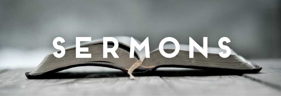 "A bible lays open at a table and the word ""SERMONS"" is across the picture in big, bold letters."